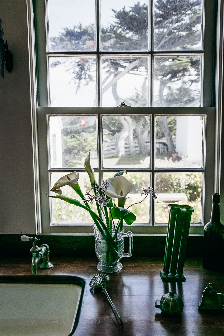 A countertop with a flower vase in front of a window overlook a backyard in winter.