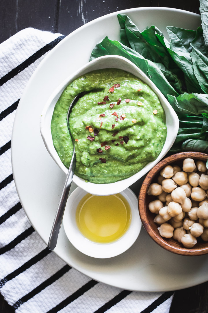 chickpea pesto in a white ramekin on a white plate with a silver spoon