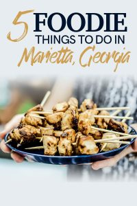 "Two hands holding a blue plate with barbecued chicken with the words ""things to do in Marietta, Georgia."""