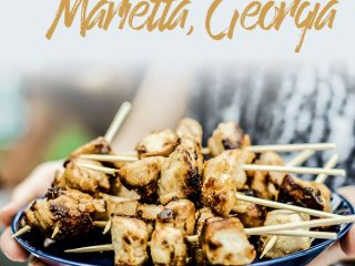 """Two hands holding a blue plate with barbecued chicken with the words """"things to do in Marietta, Georgia."""""""