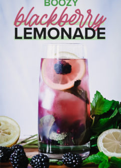"a glass of lemonade with blackberries and lemons inside on a wooden table with a blue background and the words ""boozy blackberry lemonade"" in purple and black writing"