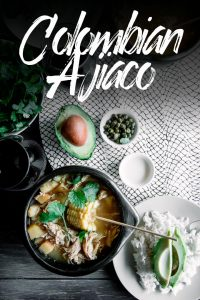 """A chamba pot with Colombian ajiaco on a wood table with a side of rice, avocado, cream, and cilantro and a glass of wine and the words """"Colombian Ajiaco"""""""