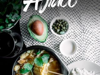"A chamba pot with Colombian ajiaco on a wood table with a side of rice, avocado, cream, and cilantro and a glass of wine and the words ""Colombian Ajiaco"""