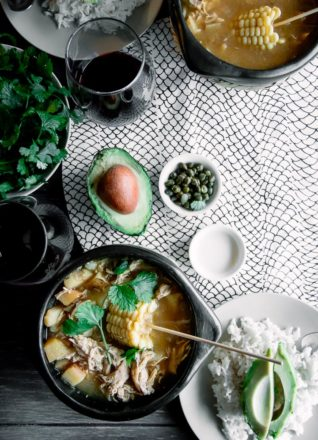 A chamba pot with Colombian ajiaco on a wood table with a side of rice, avocado, cream, and cilantro and a glass of wine.