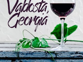 """A glass of wine with a green vine on a blue dresser with the words """"5 foodie things to do in valdosta, georgia."""""""