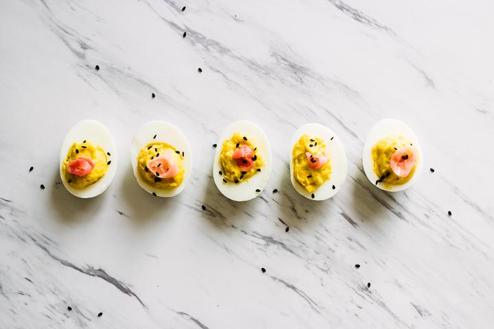 A wasabi ginger deviled eggs with pickled ginger on top on a slab of marble garnished with black sesame seeds.