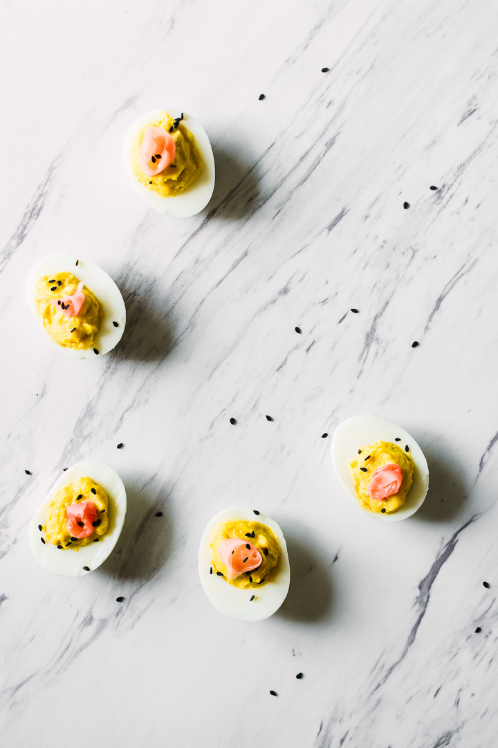 A wasabi ginger deviled eggs with pickled ginger on top on a slab of marble garnished with black sesame seeds.