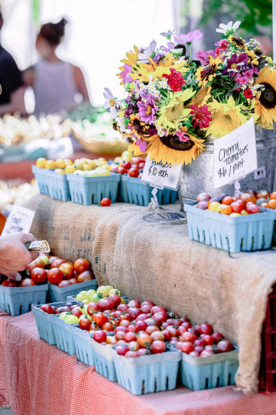 A farmers markets with bins of tomatoes and flowers.