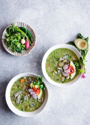 Three bowls of pozole verde soup on a blue table.