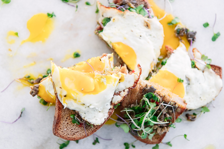 A piece of bread with olive tapenade, microgreens, and a broken sunny eggs on a piece of marble.