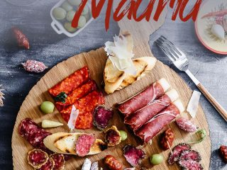 """A round cheese and charcuterie board with Spanish finger foods on a blue table with the words """"five foods you must eat in madrid"""""""
