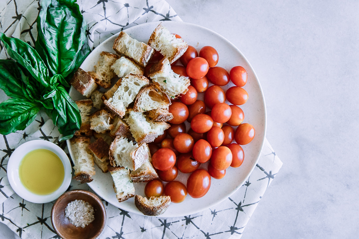 Tomatoes, ciabatta bread, and fresh basil on a white plate on a white table.