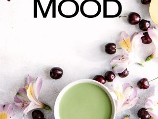 A cup of matcha on a white table with red cherries, mango, and pink flowers.