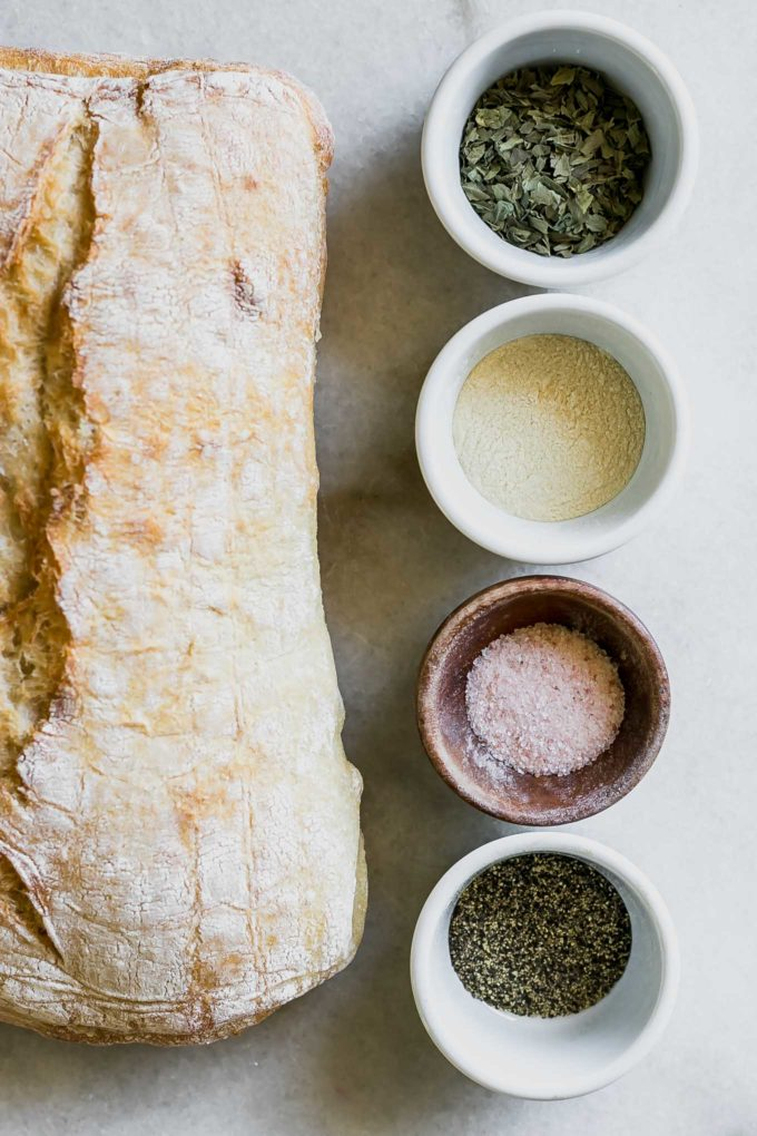 ciabatta bread and bowls of dried herbs, salt, pepper, and oil on a white table