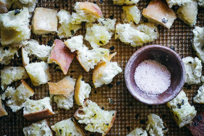 baked ciabatta croutons on a baking sheet with a bowl of salt