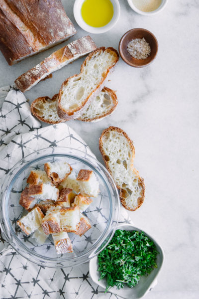 Sliced ciabatta bread on a table with fresh herbs and salt for homemade croutons recipe.