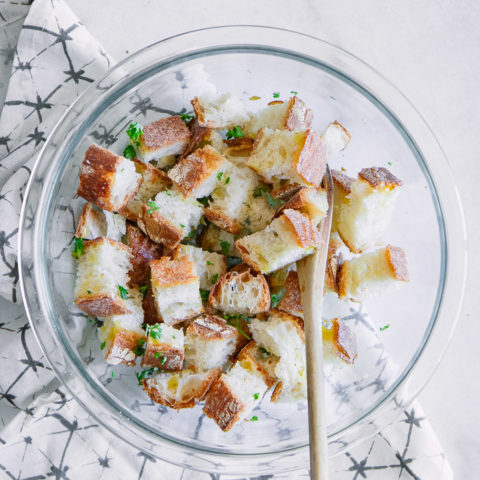 A bowl of bread cubes to be made into homemade croutons on a white table.