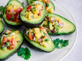 "A stack of cut avocados stuffed with salsa on a white table with the words ""pineapple pico de gallo avocado cups"" in black text."