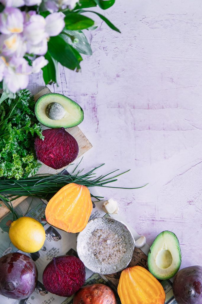 Beets, avocado, and herbs on a pink table.