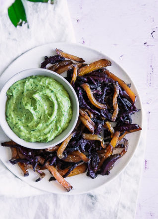 Roasted beet fries on a white plate with green dip on a pink table.
