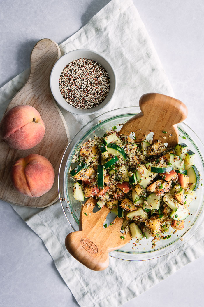 A large glass bowl with a peach and quinoa vegan salad with peaches on a cutting board.