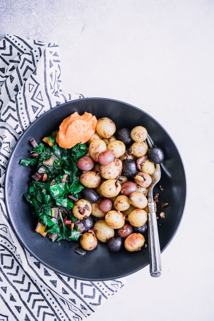 A black bowl with breakfast potatoes, cooked greens, and garlic aioli.