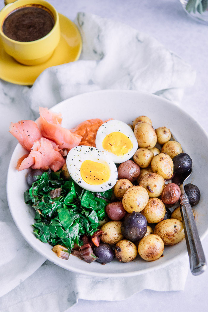 A brunch bowl with salmon, potatoes, greens, aioli, and egg on a white table with a yellow espresso cup.