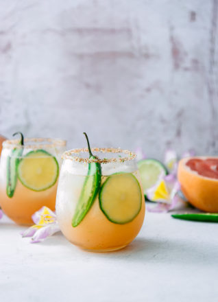 A margarita with grapefruit, lime, and orange with spicy jalapenos on a white table with flowers.