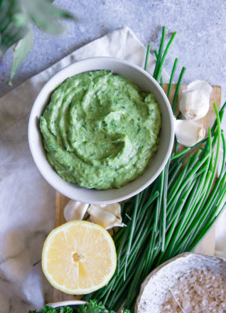 A bright green dip in a white bowl with a lemon and chives on a blue table.