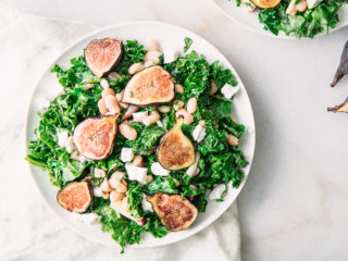 A green salad with kale, figs, white beans, and goat cheese on a white plate.