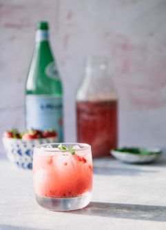 A strawberry and mint sparkling soda on a blue table with a bowl of strawberries and a bottle of sparkling water in the background.