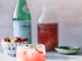 """A sparkling water with strawberries and mint on a blue table with a pink background and the world """"Strawberry Mint Spritzer"""" in black writing."""
