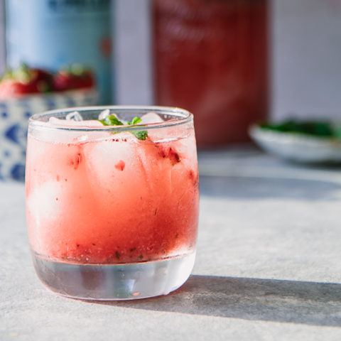 A glass of sparkling water with strawberries and mint on a blue table.