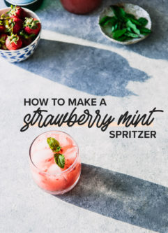 a cocktail glass filled with sparkling water, crushed strawberries, and mint on a blue table with sunlight beaming and a bowl of strawberries and a plate of mint leaves