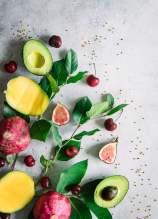 An arrangement of superfoods on a blue table, including mangos, beets, figs, cherries, and avocados.