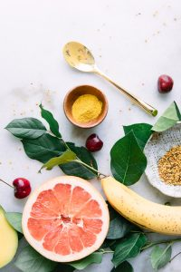 A flatlay of yellow superfoods including banana, grapefruit, turmeric, and bee pollen on a marble table.