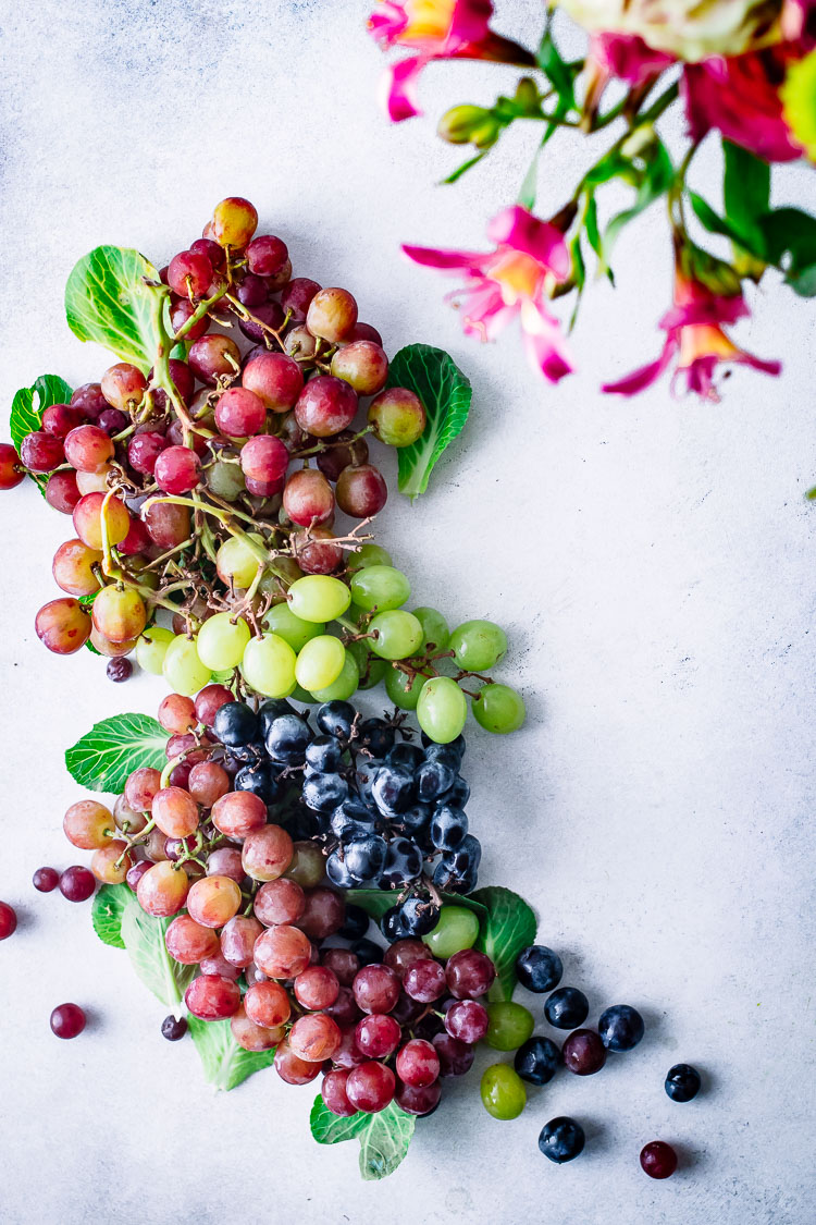 Bunches of green, red, and purple grapes on a white table with pink flowers.
