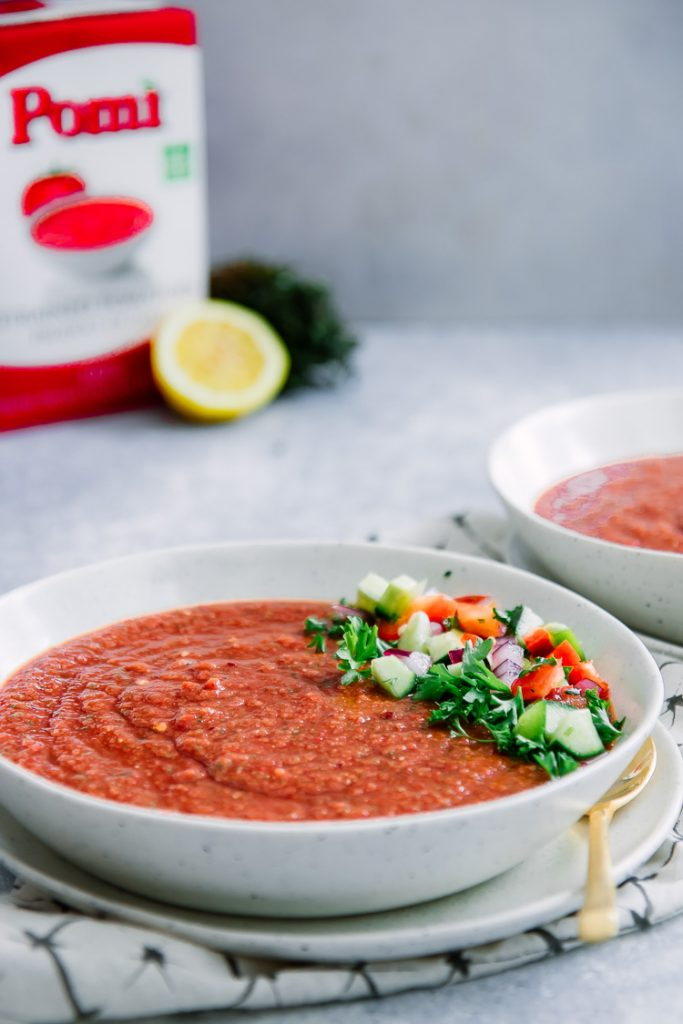 A bowl of red tomato cucumber gazpacho on a blue table with a box of Pomi tomatoes in the background.