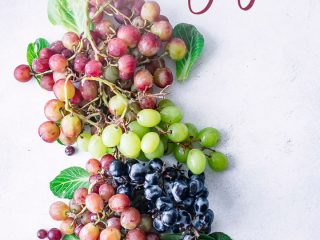 """Bunches of mixed red, green, and purple grapes on a white table with the words """"superfood spotlight grapes"""" in black writing."""