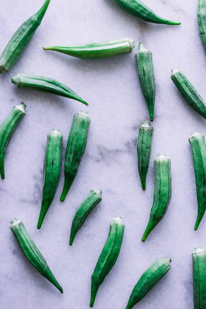 Assorted okra pods on white marble.