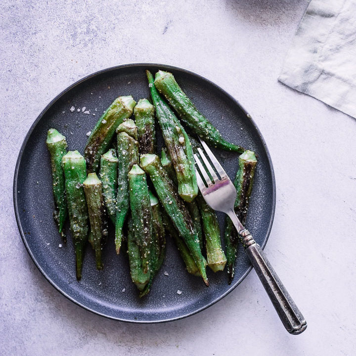 Pan fried okra on a blue plate with a silver fork.