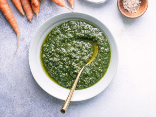 A white bowl of pesto on a white table table.