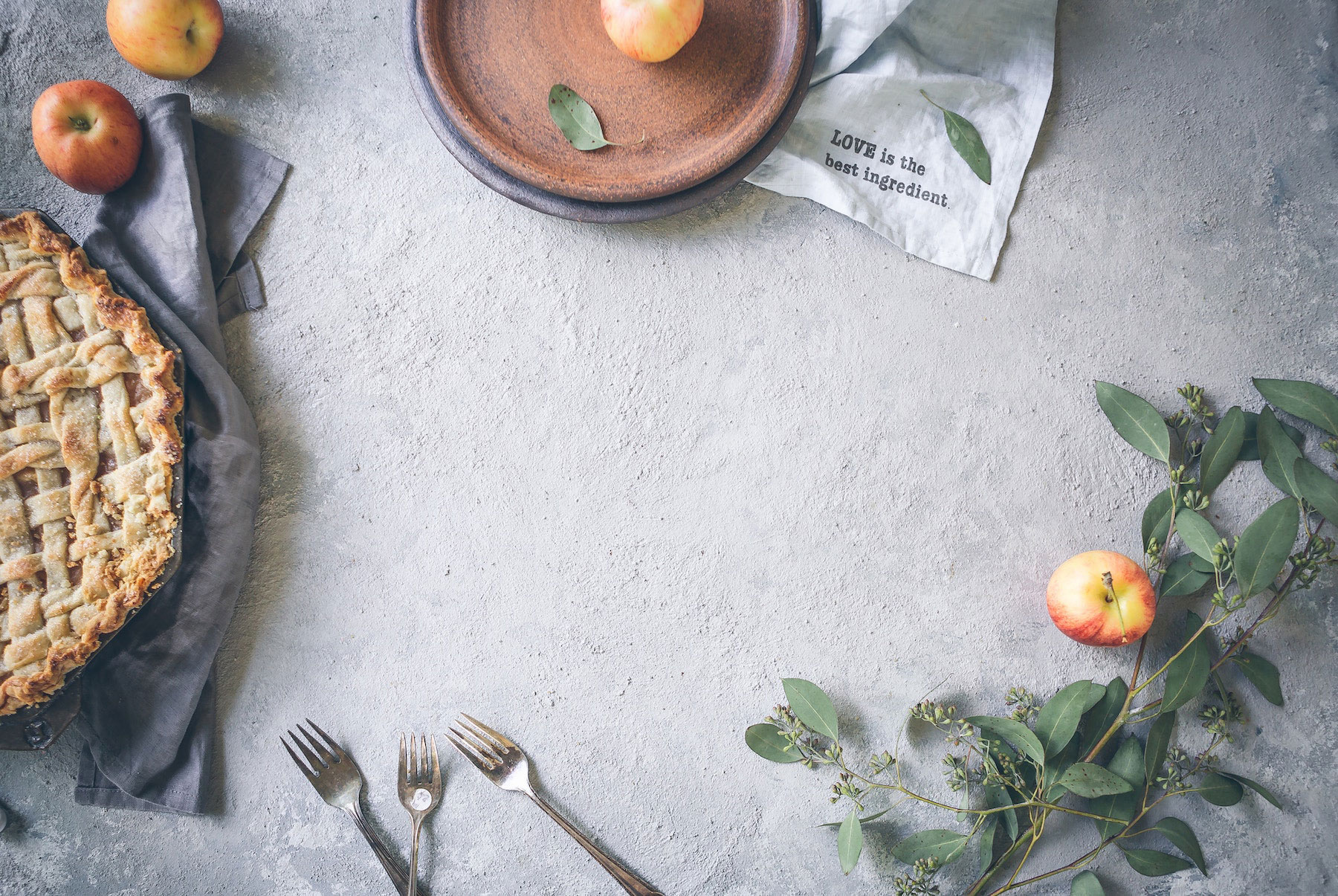A fall grey table with a pie and apples.
