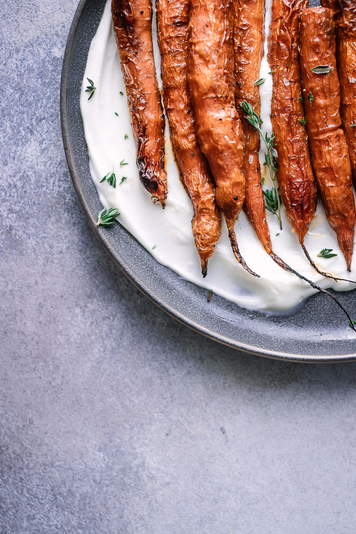 Roasted carrots in a creamy yogurt on a blue plate.