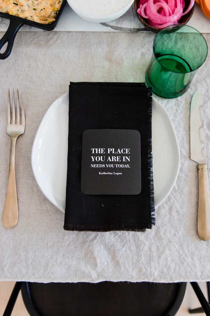 A photo of a white plate with a black napkin with a green glass.