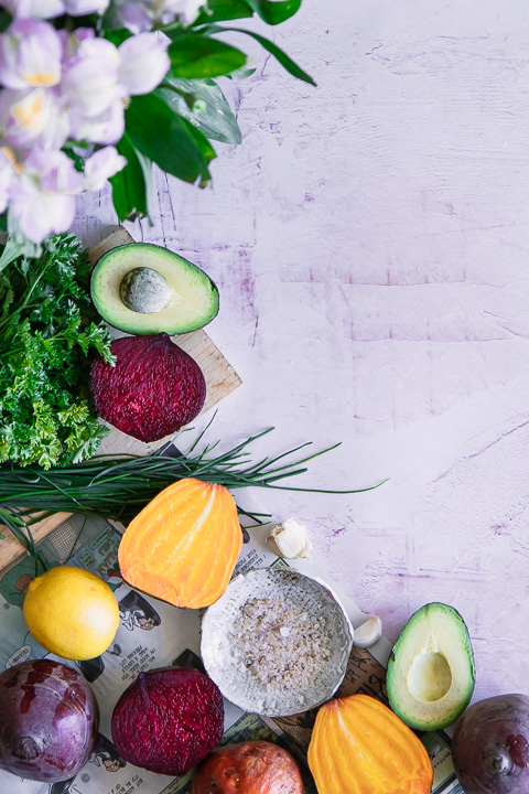 red beets, golden beets, avocado, lemons, and kale on a pink table