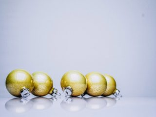 gold holiday ornaments on a white table
