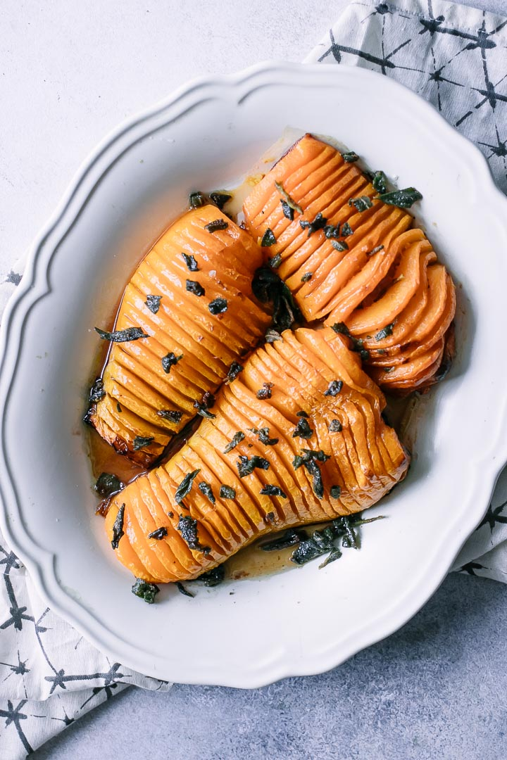 Hasselback cut butternut squash on a white plate