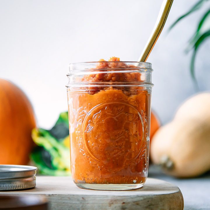 A jar of homemade pumpkin puree on a blue table with a gold spoon
