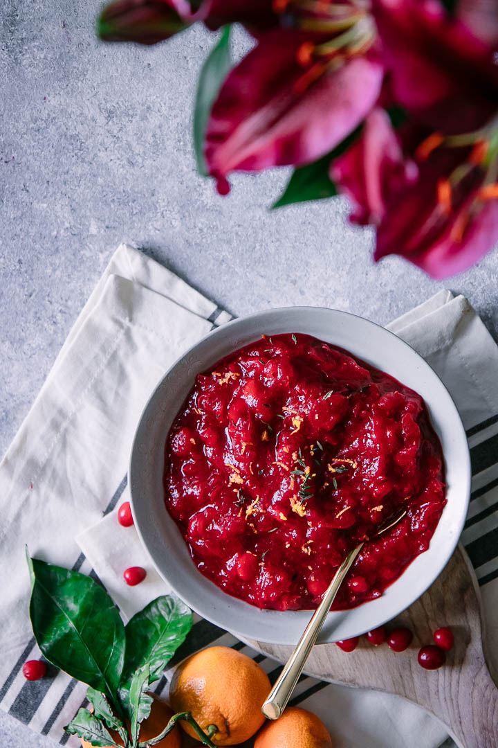 A bowl of red cranberry sauce on a Thanksgiving table
